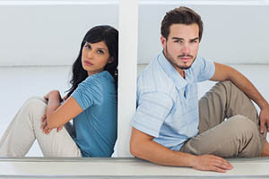 Unhappy couple are separated by white wall and looking camera
