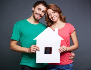 Portrait of young couple holding paper house and looking at camera